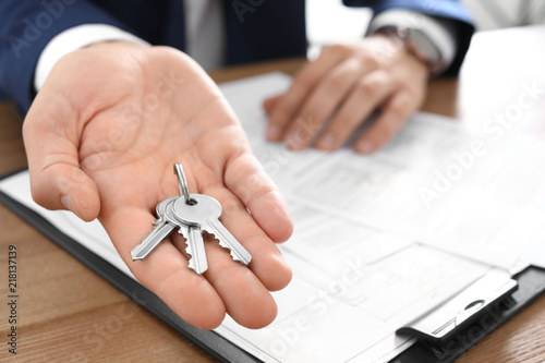 Foto  Real estate agent with keys at table in office, closeup