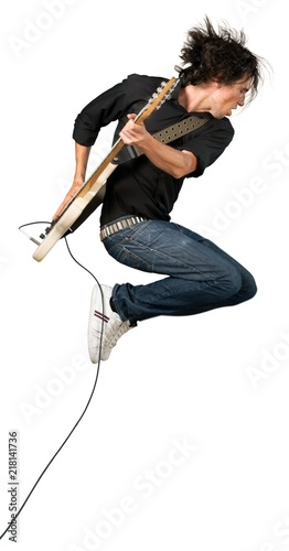 Portrait of a Musician Jumping while Playing an Electric Guitar - 218141736
