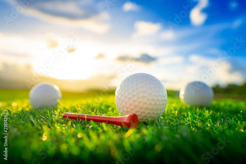 close up the golf ball and red tee pegs on the green background with sunset