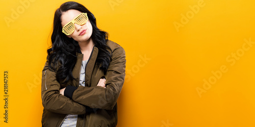 Fotomural Fashionable woman in a bomber jacket on a golden yellow background