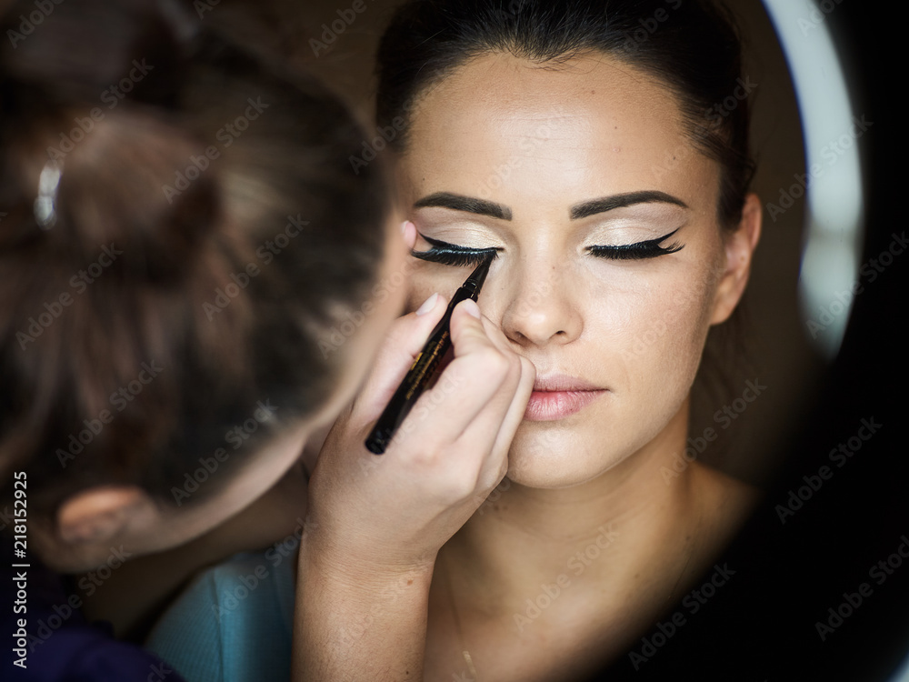Fototapeta Make up artist doing professional make up of young woman.