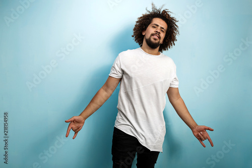 Fotografija  A curly-headed brunet man with flying hair is wearing an asymmetric white T-shirt