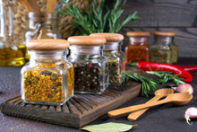 Products For Cooking In Kitchen, Kitchen Utensils, Herbs, Colorful Dry Spices In Glass Jars On Dark Background