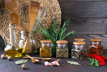 Kitchen Utensils, Herbs, Colorful Dry Spices In Glass Jars On Dark  Background