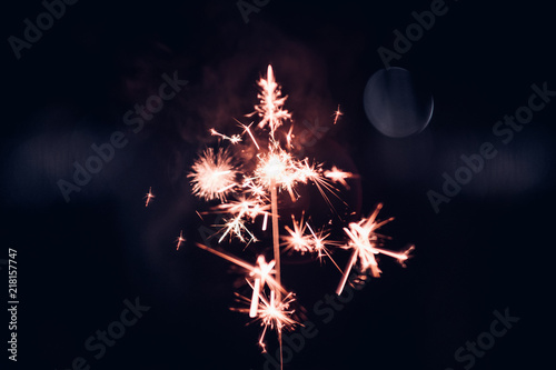 Hand holding burning Sparkler blast on a black background at night,holiday celeb Canvas-taulu