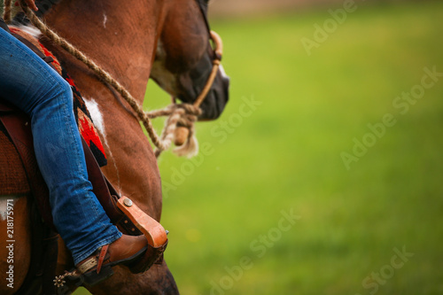 Fotografía Horse, western pony, close-up of the rider's leg in the stirrup with spurs!