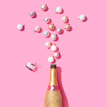 Golden Glittering Champagne Bottle With Christmas Baubles Decoration On Pink Background. Flat Lay. Minimal Party Concept.