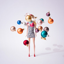 Girl Doll In Silver Glittering Dress With Colorful Christmas Baubles Decoration. Creative Minimal Fashion Concept.