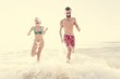 Cheerful couple running at the shore