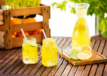 Mason Jar Glasses Of Homemade Lemonade With Slices Of Lemon On Wooden Table Outside