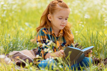 Portrait Of Adorable Red Hair Child Reading Book While Sitting In Summer Field