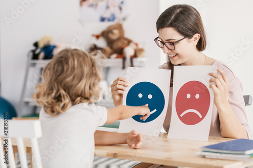 Fotografia  Young kid pointing at graphic with a smiley face during a psycho