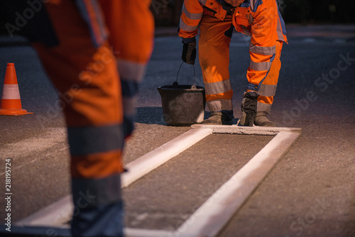 Fototapeta Traffic line painting. Workers are painting white street lines on pedestrian crossing