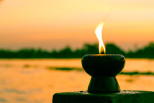 Candle Light Fire Lamp Nearby Abstract Background River During Sunset Or Sunrise In Countryside. Melting Candlestick In Evening Twilight. Religion Abstract Concept.