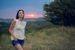 girl in a white jacket at sunset in the field stands