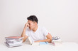 Stressed Young Man Studying Surrounded By Stack Of Book