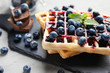 canvas print picture - Delicious waffles with blueberries and jam on slate plate, closeup