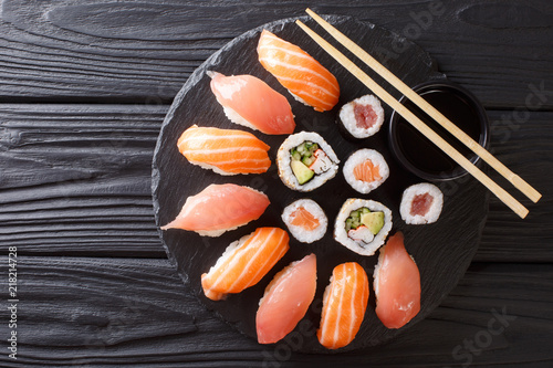 Sushi rolls set served on black stone slate on dark background. horizontal top view