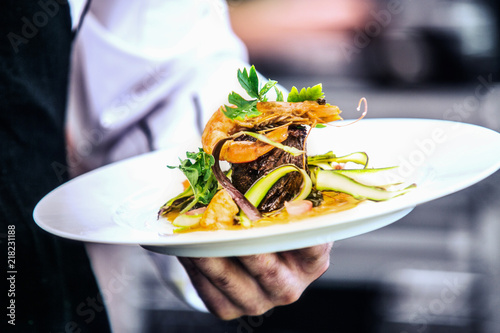 Fototapeta Modern food stylist decorating meal for presentation in restaurant. Closeup of food stylish. Restaurant serving. Close-up on the hand of a waiter carrying food obraz