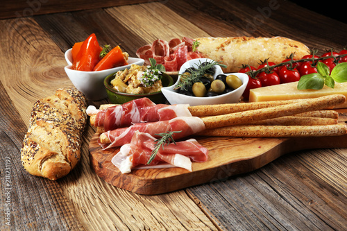 Italian antipasti wine snacks set. Cheese variety, Mediterranean olives, crudo, Prosciutto di Parma, salami and wine in glasses over wooden grunge background.
