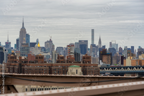 View Of Midtown Manhattan From Brooklyn Bridge On A Cloudy