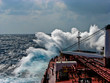 canvas print picture - Waves in the Atlantic Ocean, strong wind, the tanker is flooded with water.