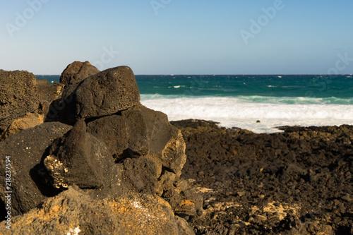 Deurstickers Canarische Eilanden Black volcanic rocks stacked on Lanzarote beach with waves background