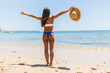 Woman on Beach standing with arms outstretched against turquoise sea. Rear view of female wearing bikini with raised hands. Carefree tourist is enjoying vacation at beach.