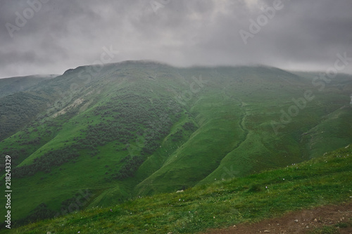 Poster Donkergrijs panorama of the green hill in caucasus mountains during misty weather