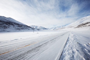 empty highway through snow moutain