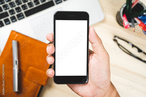 Man hand holding mobile smartphone isolated white screen for mockup design on laptop, notebook and eyeglasses background
