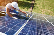 canvas print picture - Professional worker installing solar panels on the green metal construction, using different equipment, wearing helmet. Innovative solution for energy solving. Use renewable resources. Green energy.