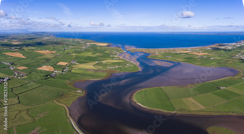 Fototapeta panoramic aerial view surrounding farmland and river flowing into the Atlantic ocean on the west coast of Ireland   obraz