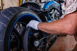 Side view portrait of man working in garage repairing motorcycle. Hands close up