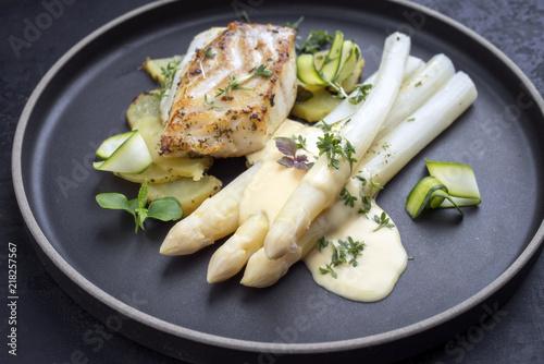 Modern Style deutsches Barsch Fisch Filet mit weißen Spargel in Hollandaise Sauce mit Bratkartoffel als Draufsicht auf einem Teller