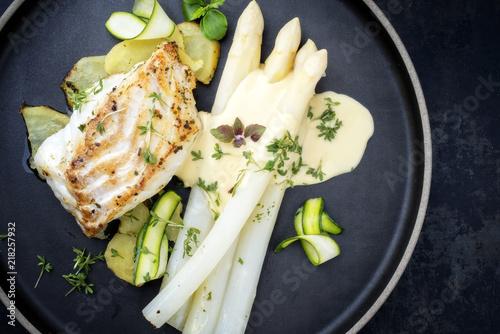 Modern Style deutsches gebratenes Kabeljau Fischfilet mit weißen Spargel in Hollandaise Sauce mit Bratkartoffel als Draufsicht auf einem Teller