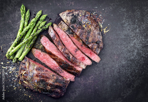 Fotografie, Obraz  Barbecue dry aged wagyu flank steak sliced with green asparagus as top view on a