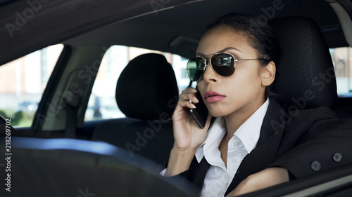 Lady in sunglasses sitting in car and talking on cellphone, police agent on duty
