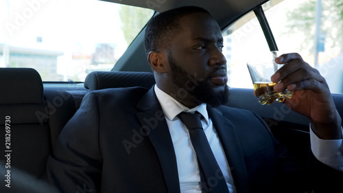 Fotografie, Obraz Thoughtful African American man sitting on back seat of car with alcohol drink
