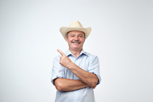 Your Advertising Here. Studio Portrait Of Handsome Senior Man In Blue Shirt And Cowboy Hat Showing Copy Space