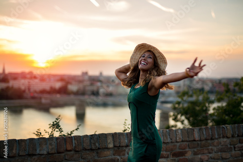 Photo  Beautiful young woman playing with her hat at sunset while smiling