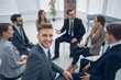 young employee sitting in a circle with business team