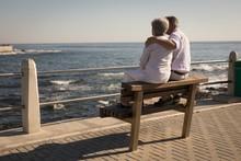 Senior Couple Sitting On Bench Near Sea Side