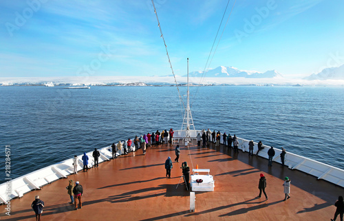 Photo Stands Antarctic Tourist on Cruise Ship Deck Heading to Anarctic Peninsula, Ice covered Land Ahead