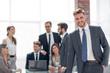 smiling businessman standing near the desktop