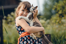 Girl In A Dress Hugs A Little Cat