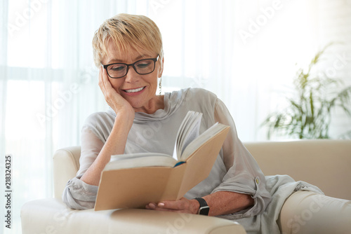Obraz na plátně Senior blond woman in glasses resting on sofa and reading a book