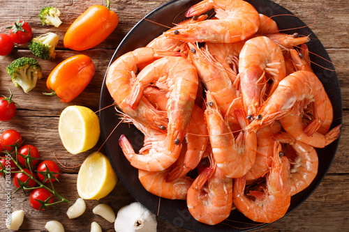 Dish with large shrimp and fresh vegetables close-up on a table. Horizontal top view from above
