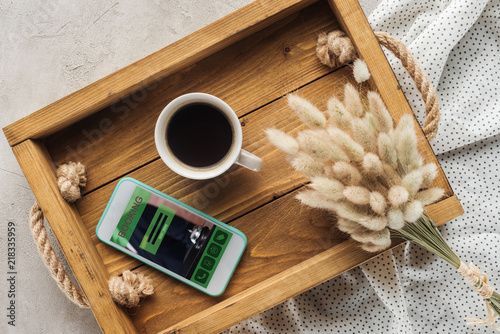 top view of cup of coffee and smartphone with booking website on screen on tray Canvas Print
