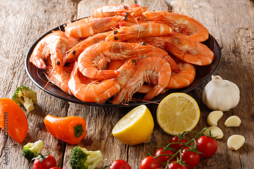 Dish with large shrimp and fresh vegetables close-up on a wooden table. horizontal